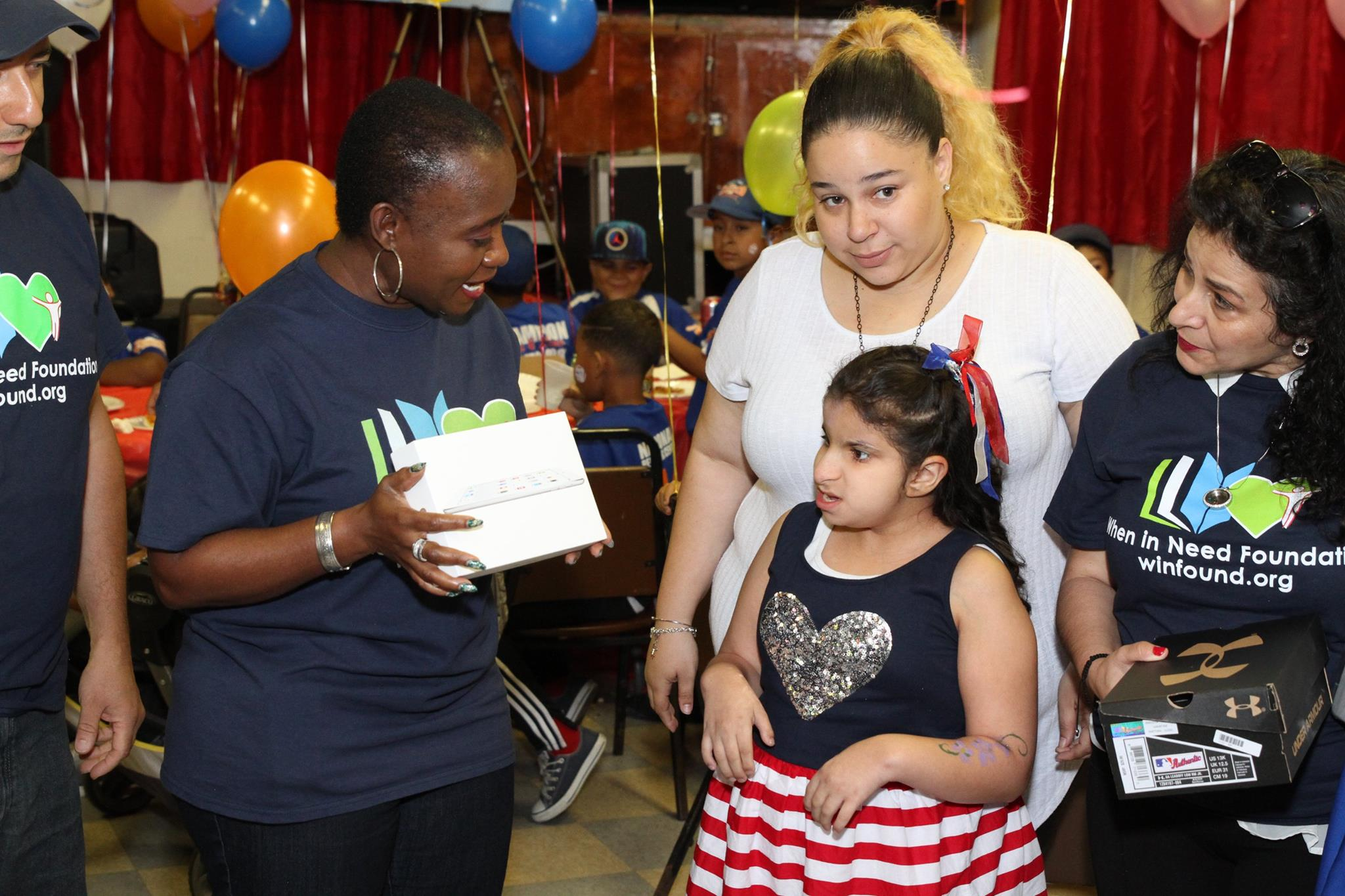 Ms. Chetachi Ecton presents young girl with Ipad